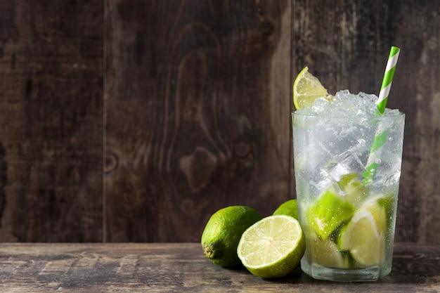 Caipirinha cocktail em vidro na mesa de madeira