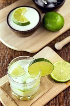 Caipirinha com ingredientes. limão, açúcar, gelo e álcool. bebida brasileira à base de cachaça