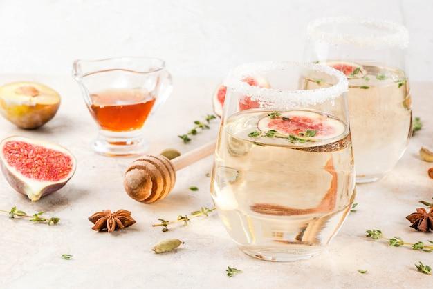 Cair frio doce vinho branco cocktail com figo, ameixa, mel e tomilho, copyspace