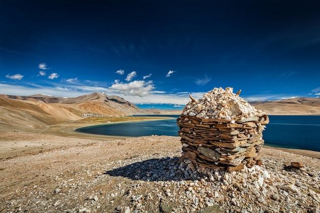 Cairn de pedra no lago tso moriri, korzok, área de changthang, ladakh, jammu e caxemira, índia