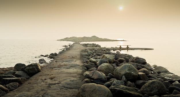 Cais cercado por pedras atravessando o mar calmo com o céu ensolarado