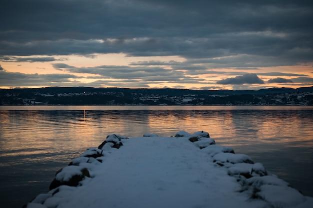Cais coberto de neve perto do mar com o reflexo do pôr do sol