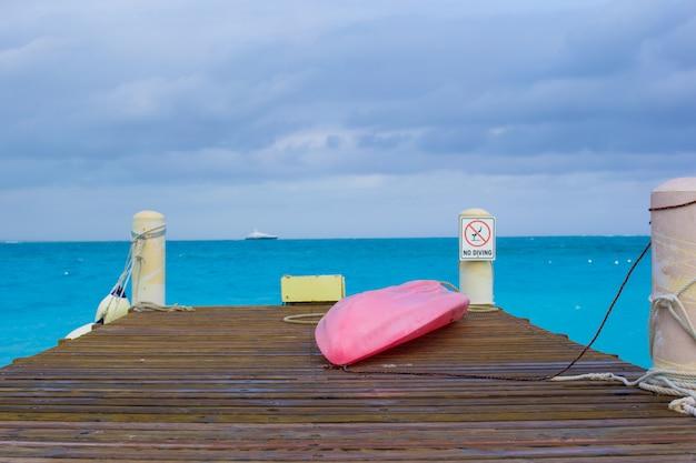 Cais com barco em uma praia tropical