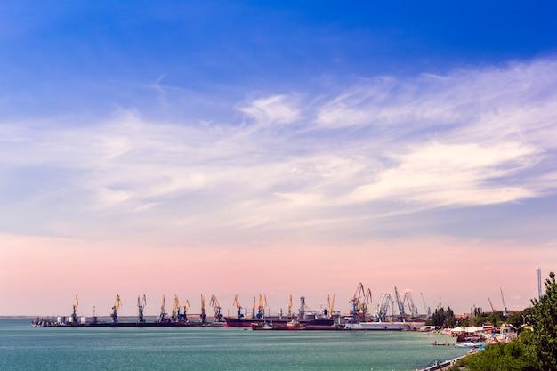 Cais com guindastes e navios ao pôr do sol