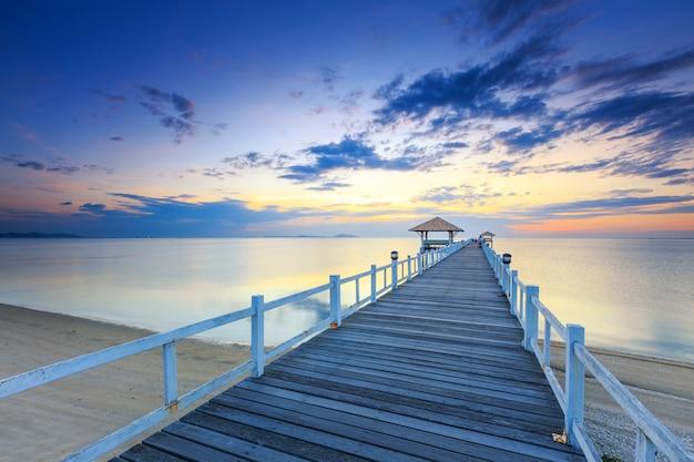 Cais da ponte de madeira velha contra o uso do céu do por do sol bonito para o fundo natural, o contexto e a cena do mar de múltiplos propósitos