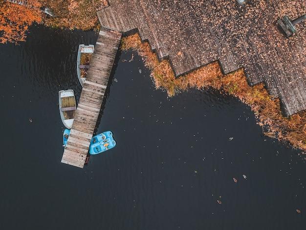 Cais da vista aérea com os barcos de madeira na costa de um lago pitoresco, floresta do outono. são petersburgo, rússia.