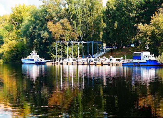 Cais de barcos dramático no fundo do rio de outono em moscou