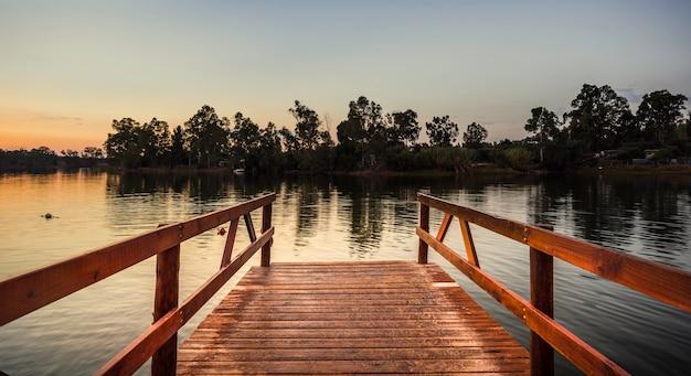 Cais de madeira avermelhada sobre o lago com águas calmas ao pôr do sol