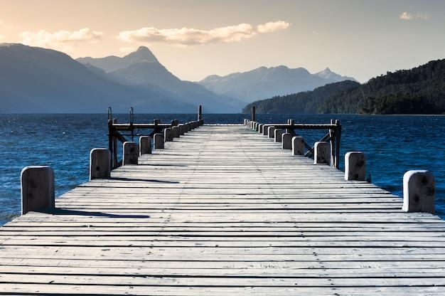 Cais de madeira em um lago com montanhas ao fundo