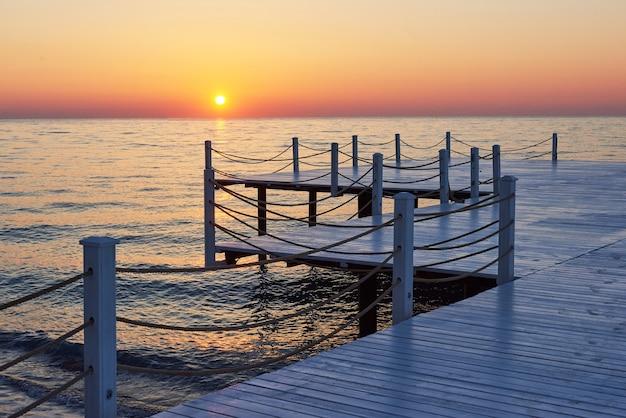 Cais de madeira em um pôr do sol laranja chique.