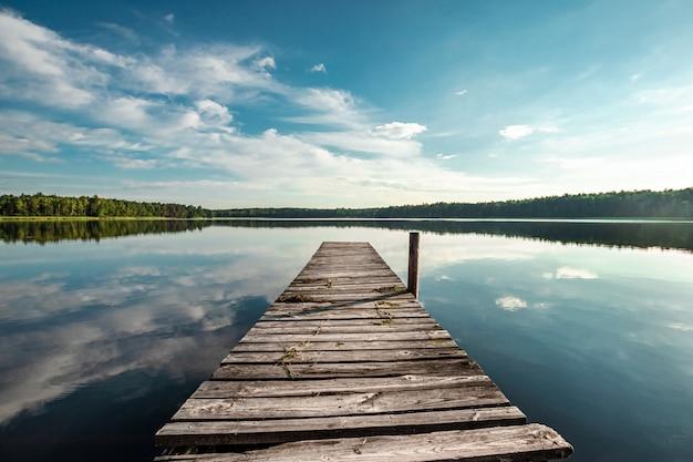 Cais de madeira na paisagem de amanhecer de verão lindo lago. copie o espaço.