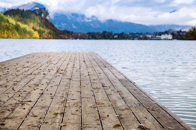 Cais de madeira no lago alpino bled, outono na eslovênia, europa