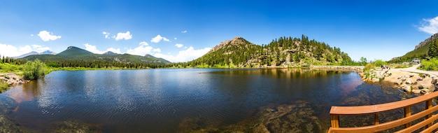 Cais de madeira no lago contra o panorama da montanha