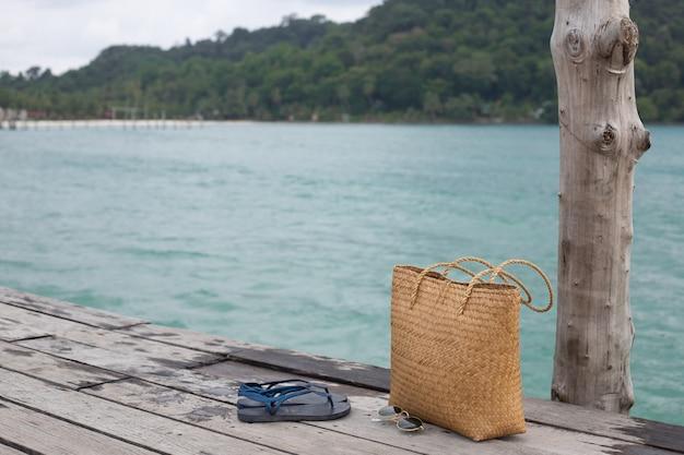 Cais de madeira praia na beira-mar e saco de verão, conceito de férias de verão