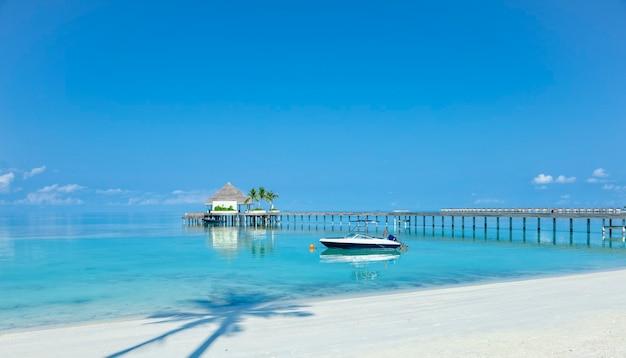 Cais de madeira sobre a água do mar azul, conceito tropical de verão