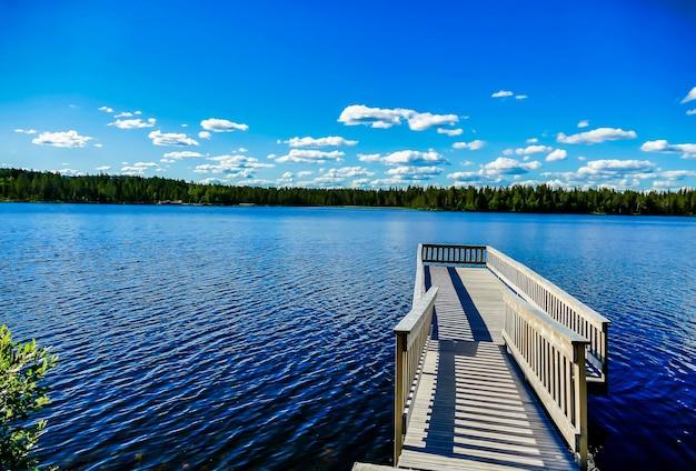 Cais de madeira sobre o belo lago com as árvores e o céu azul ao fundo na suécia