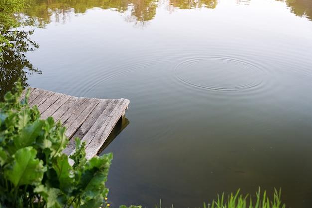 Cais de madeira velho em um lago no dia de verão ensolarado.