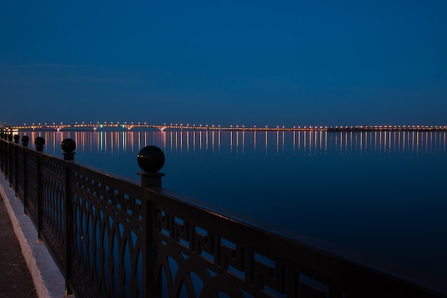 Cais de saratov da cidade da noite da mola sob o por do sol. rua luzes decorativas e lindo céu