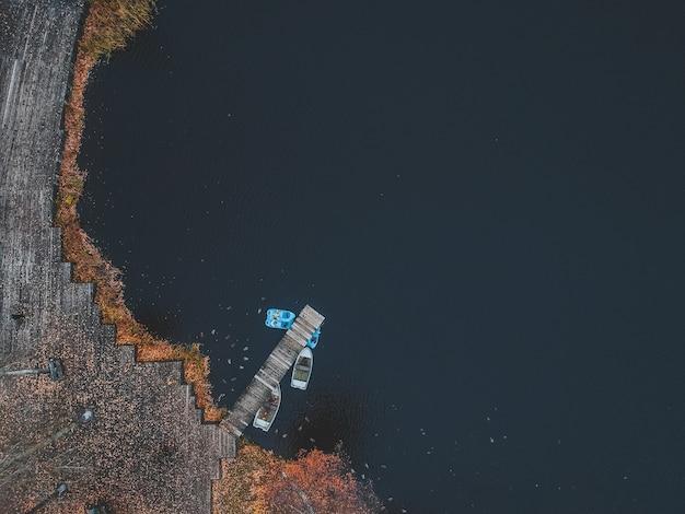 Cais de vista aérea com barcos de madeira na margem de um lago