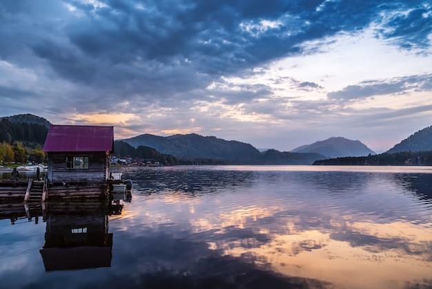 Cais do lago com um píer de madeira ao amanhecer. lago teletskoye, vila artybash, república de altai, rússia