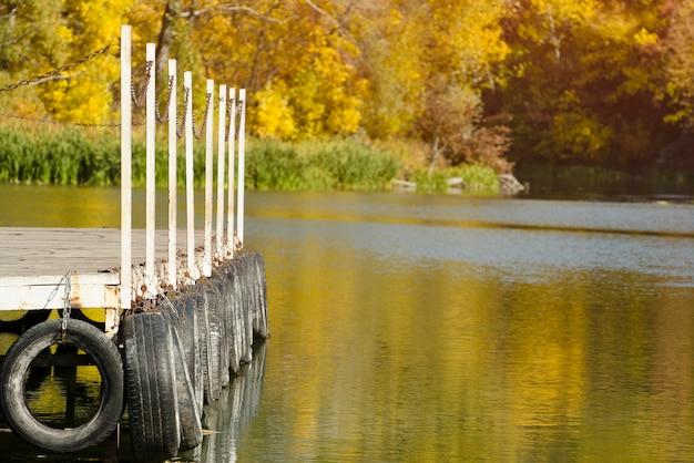 Cais do rio no fundo refletido na água das árvores amarelas de outono.