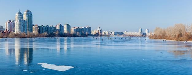 Cais em kiev lago congelado na paisagem urbana homem na pesca de inverno