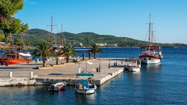 Cais largo com poucas palmeiras, três veleiros atracados, colina verde, neos marmaras, grécia
