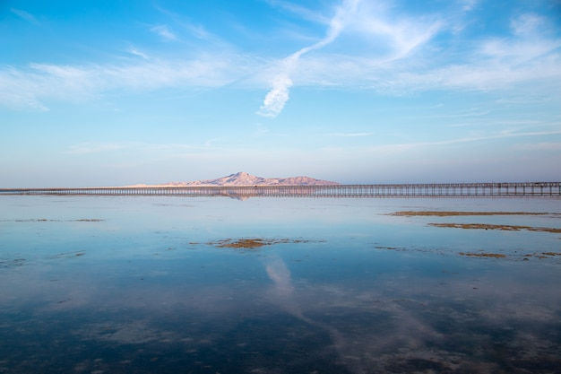 Cais longo entre o mar e as montanhas. o céu se reflete na água.