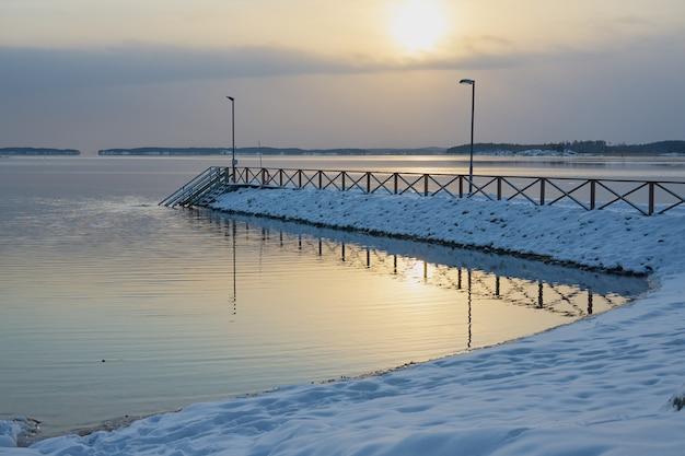 Cais na neve ao pôr do sol na costa do mar gelado.