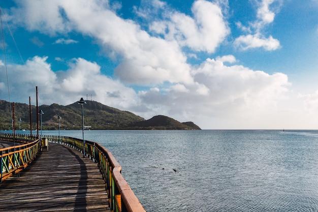 Cais no mar cercado por montanhas sob um céu azul nublado e luz do sol