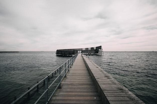 Cais que leva ao oceano sob o céu sombrio