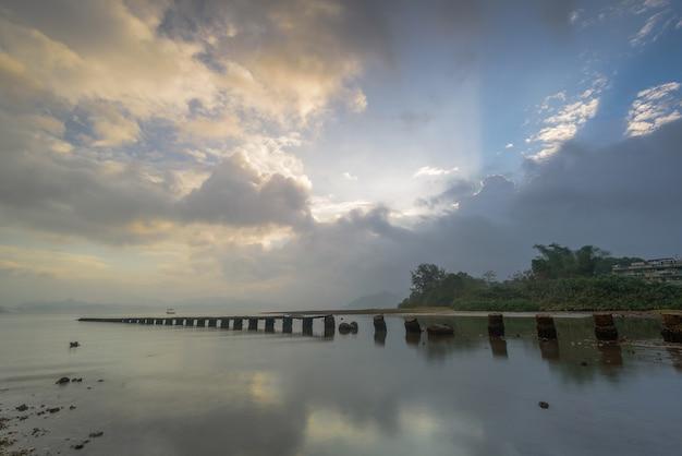 Cais quebrado no lago durante o nascer do sol em hong kong