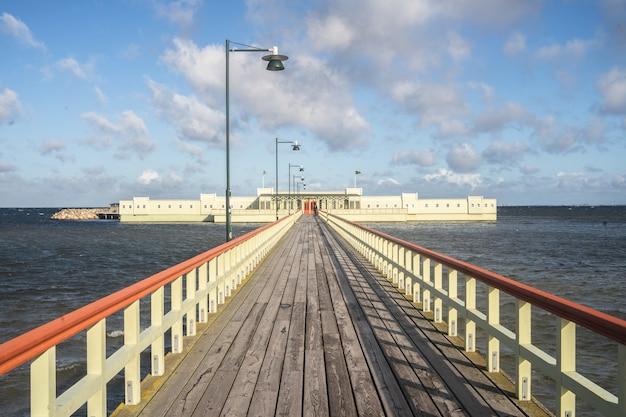 Cais rodeado pelo mar e edifícios sob um céu nublado e luz solar