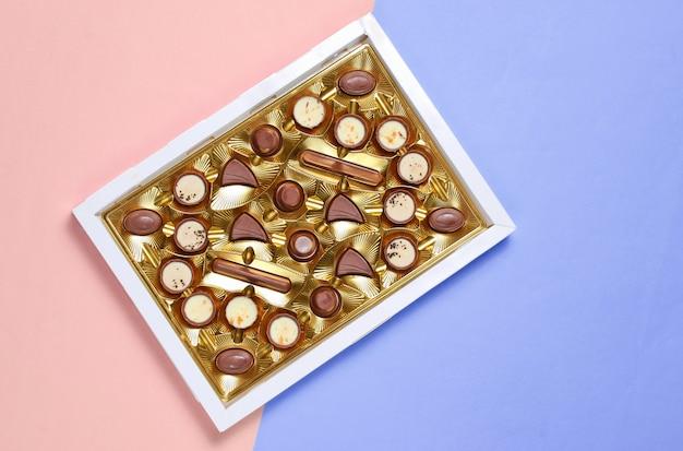 Caixa aberta com bandeja dourada com uma variedade de bombons de chocolate