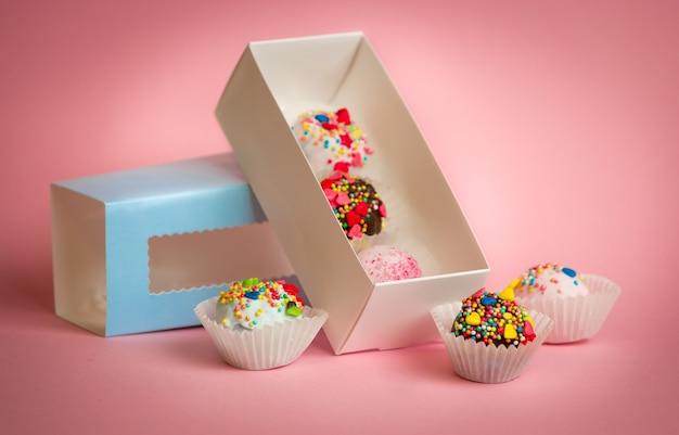 Caixa aberta com bolas de bolo caseiro com granulado colorido sobre fundo rosa