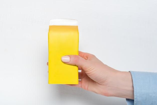 Caixa amarela ou embalagem de tetra pack em uma mão feminina