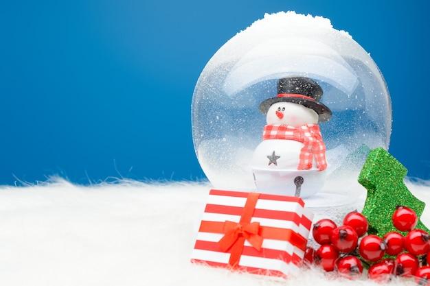 Caixa às riscas com presente de natal em arranjo com globo de neve decorativo.