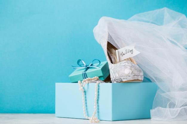 Caixa azul com sapatos de noiva em composição