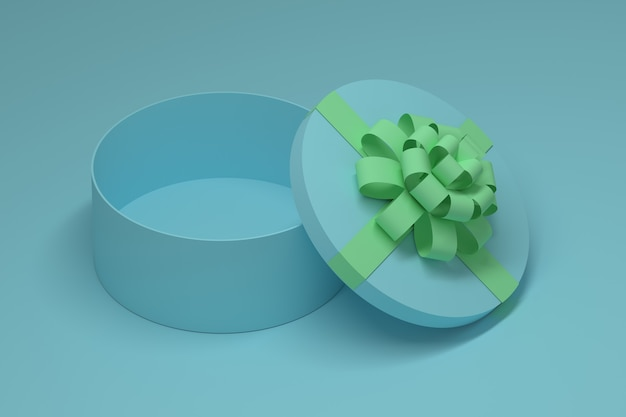 Caixa azul redonda aberta com laço verde na superfície azul