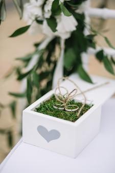 Caixa branca com design coração e alianças de casamento dentro