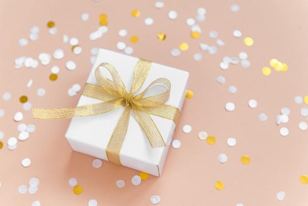 Caixa branca com fita para presente de natal com confete plano deitado sobre fundo bege