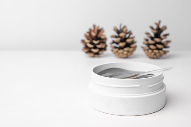 Caixa branca com tapa-olhos dourados na mesa branca com pinhas