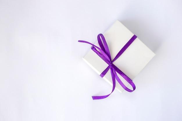 Caixa branca com um laço roxo em um fundo branco. caixa de presente, surpresa