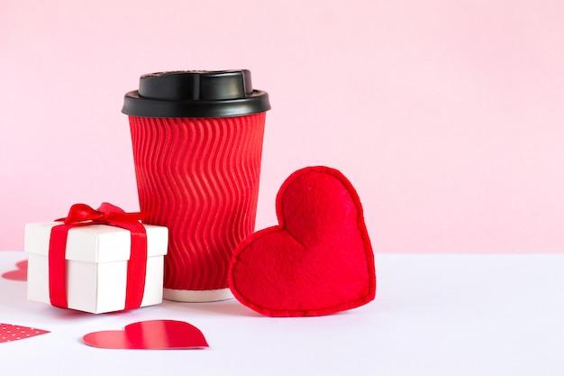 Caixa branca com um presente, xícara de café vermelha e coração vermelho