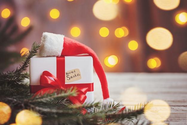 Caixa branca de natal ou presente com fita vermelha para santa secreta com chapéu de papai noel na mesa de madeira.
