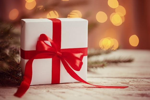 Caixa branca de natal ou presente com fita vermelha sobre fundo claro. imagem tonificada