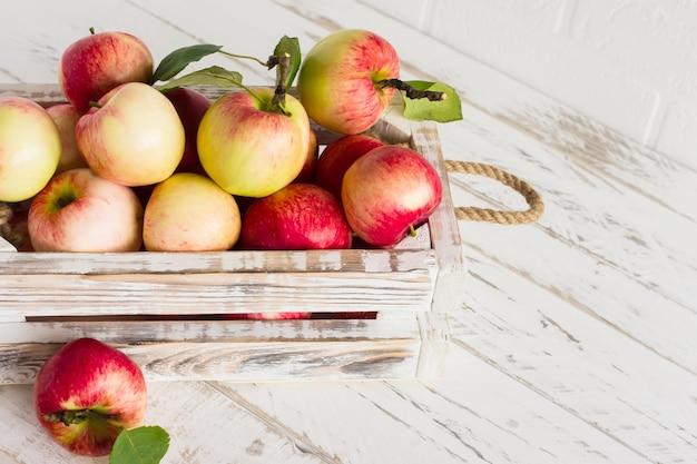 Caixa branca decorativa com maçãs maduras em uma mesa de madeira.