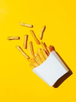 Caixa branca derramada de batatas fritas