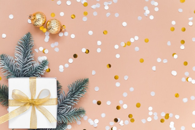 Caixa branca para presente de ano novo em fundo bege com bolas coloridas de confete ouro e abeto