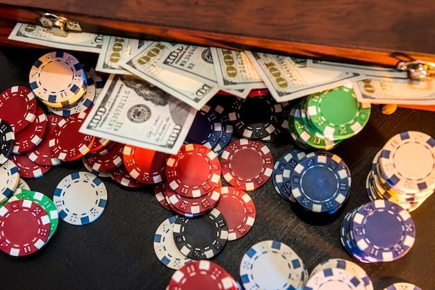 Caixa cheia de fichas, dólares e cartas de jogar em um fundo preto